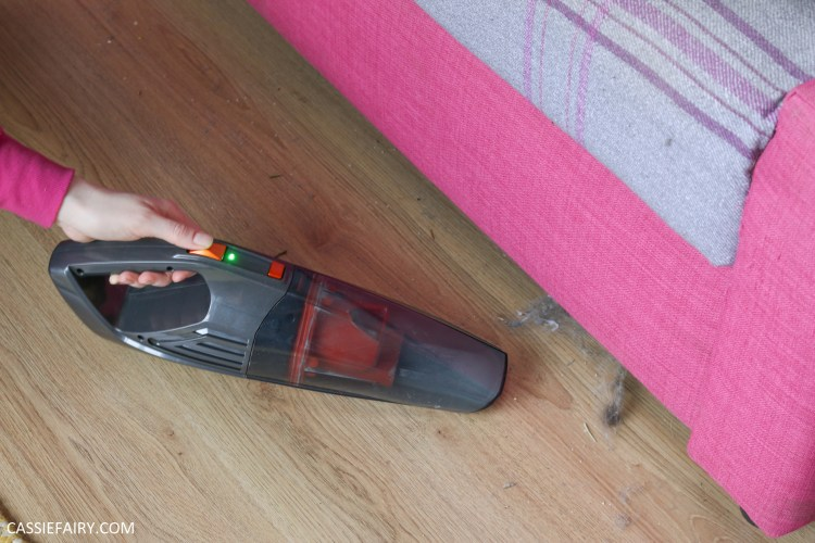 Photo of a handheld vacuum sucking up fluffy from under a sofa