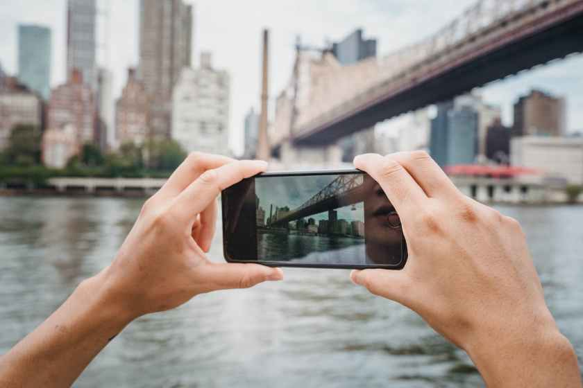 anonymous person photographing city with smartphone