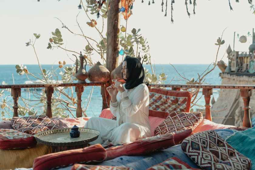 woman in white abaya and black hijab sitting with view of the sea