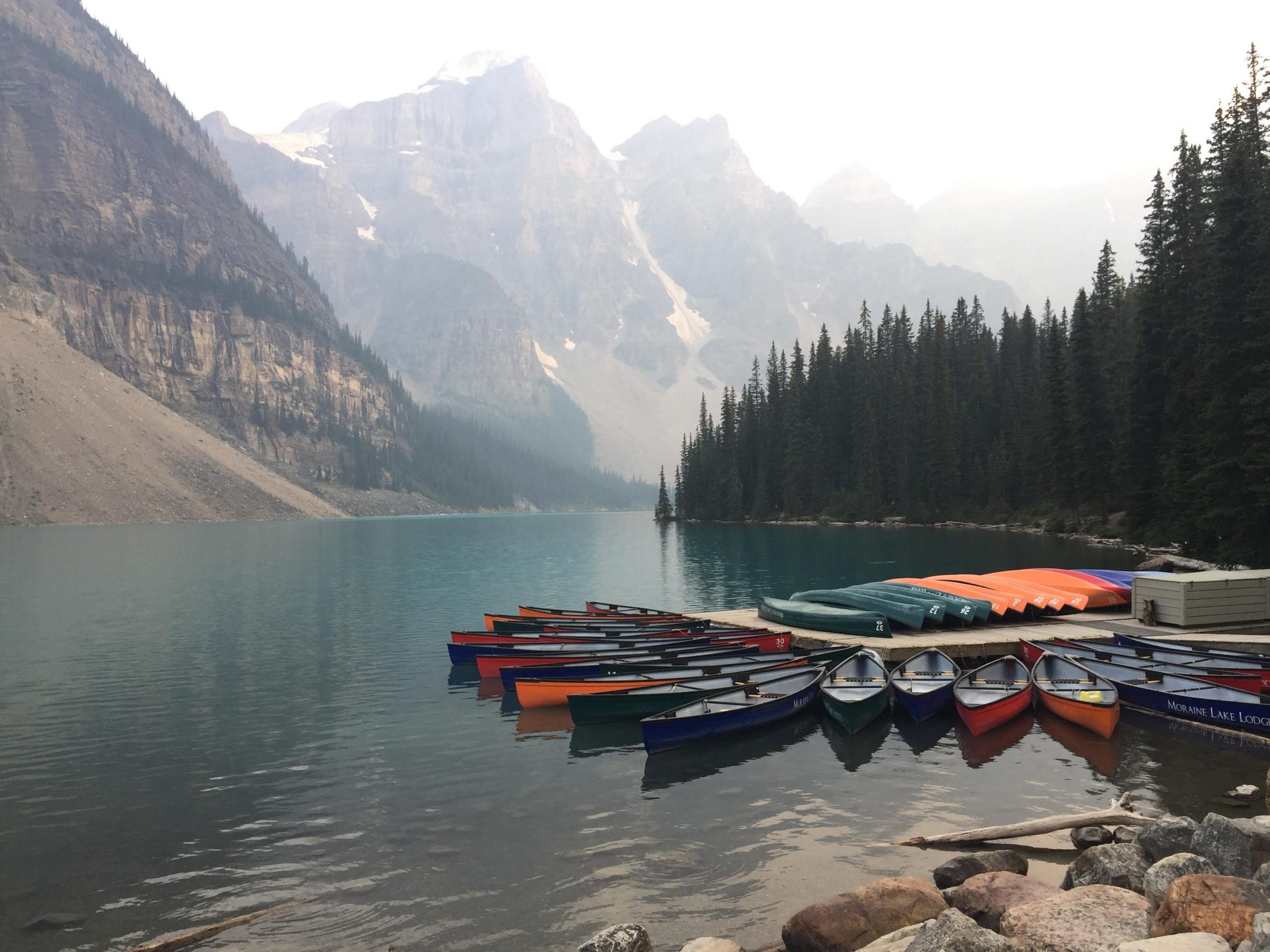 About 30 colorful canoes rest at a mountain lake dock with a gorgeous scene behind.