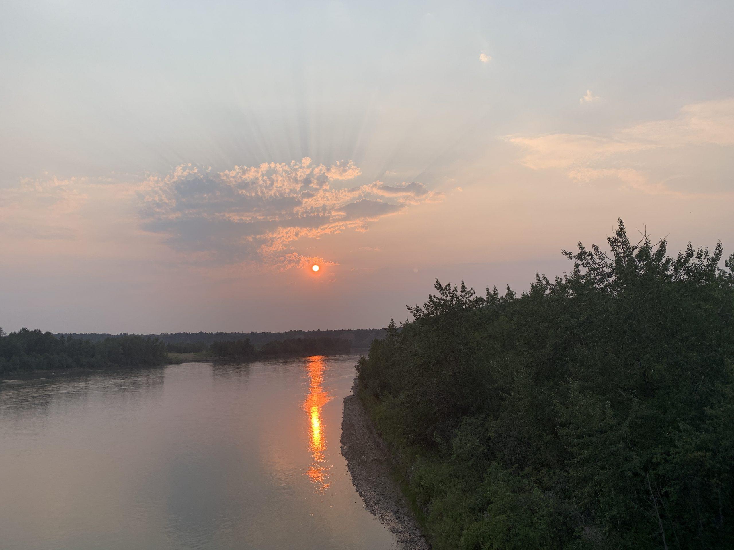 An orange hazy sun sets over a river.