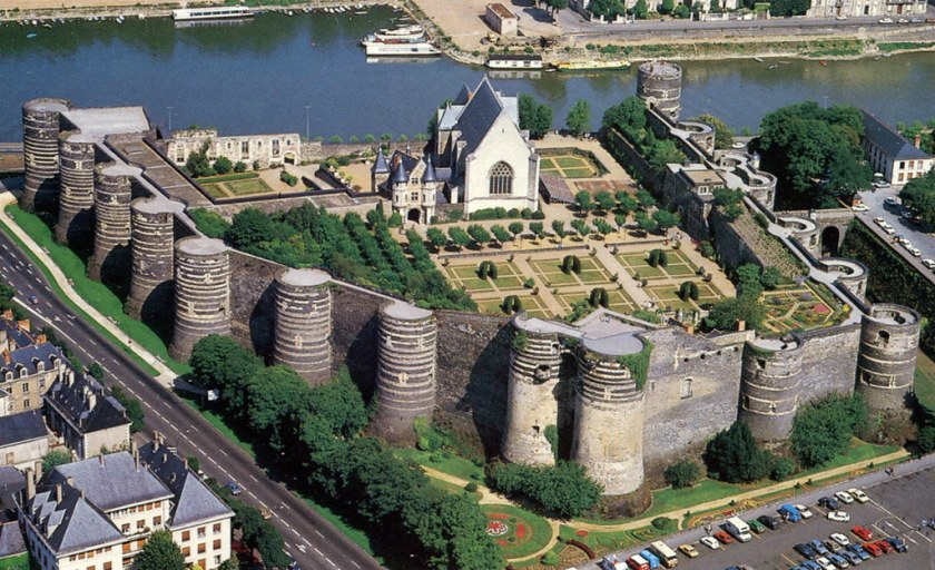 aerial view of a castle with large stone walls with many turrets. Inside there is a chapel which backs on to a river