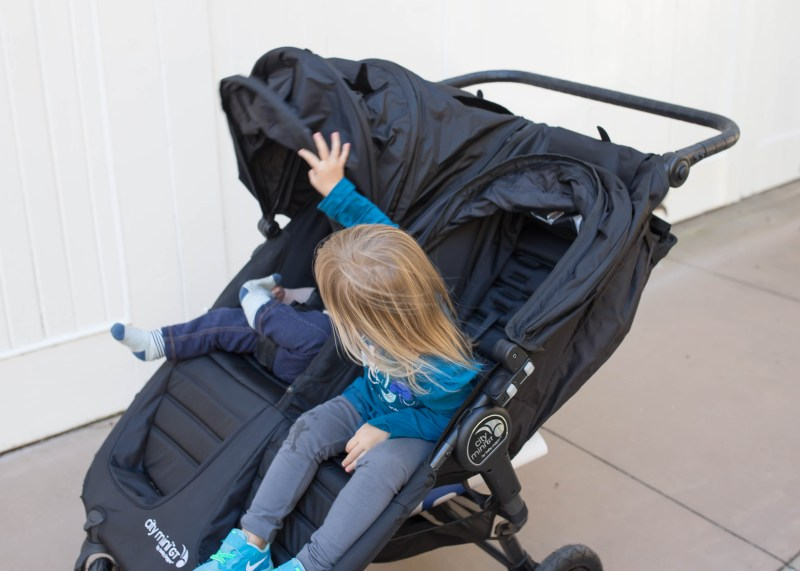 toddler and baby in double stroller