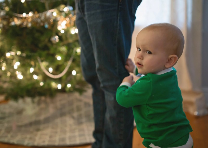 cute baby boy decorating christmas tree