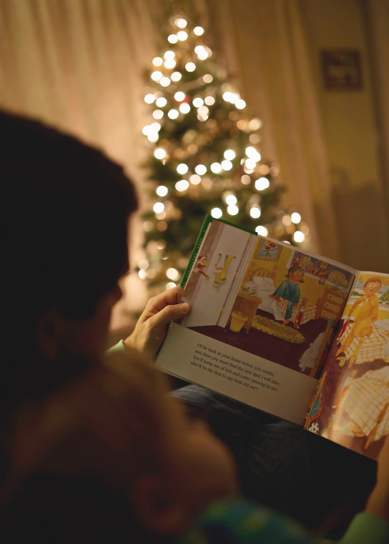 reading by the christmas tree