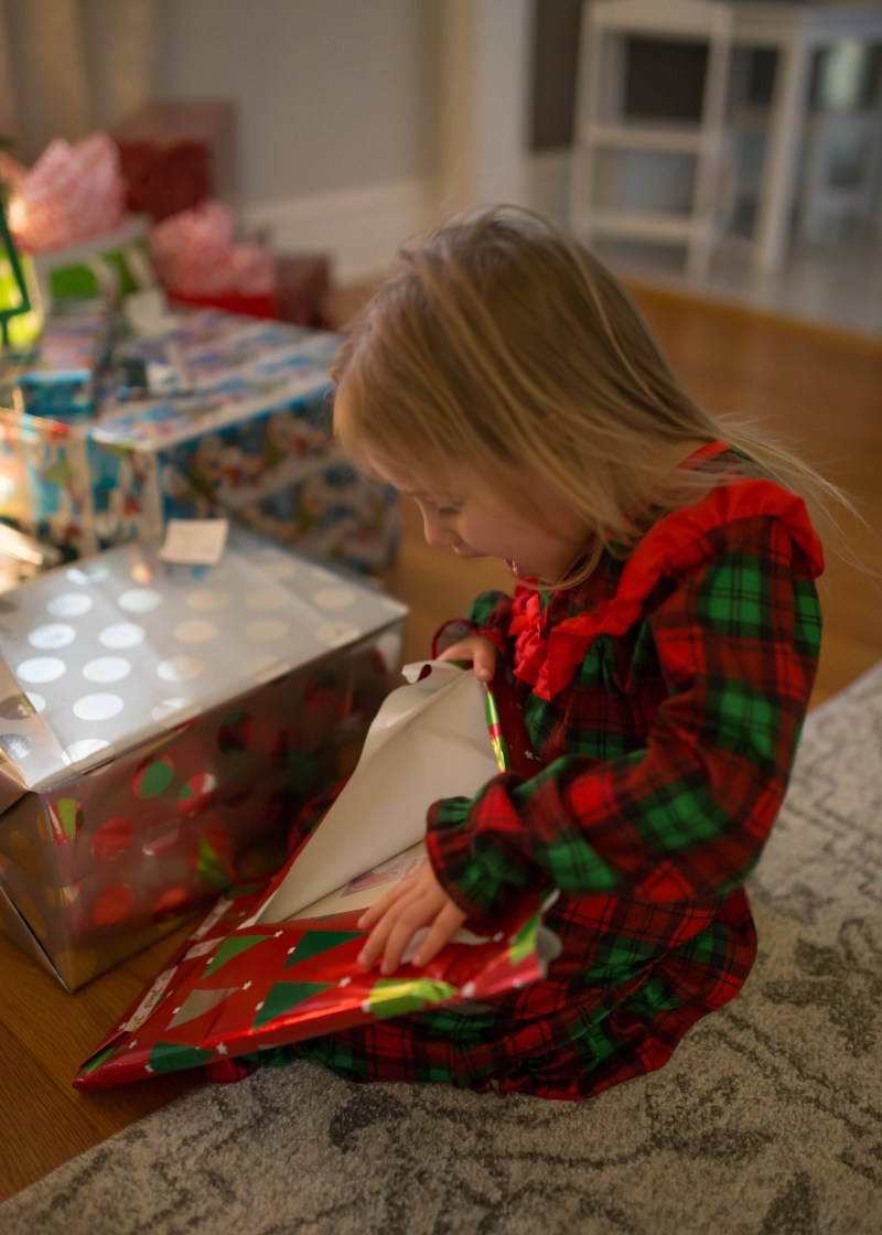 toddler girl unwrapping book surprise