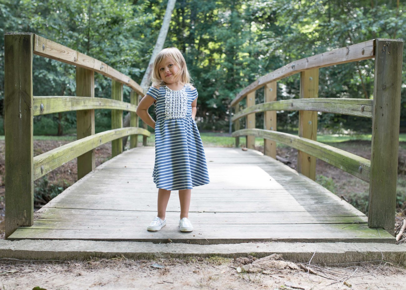 toddler girl outdoor bridge exploring dress