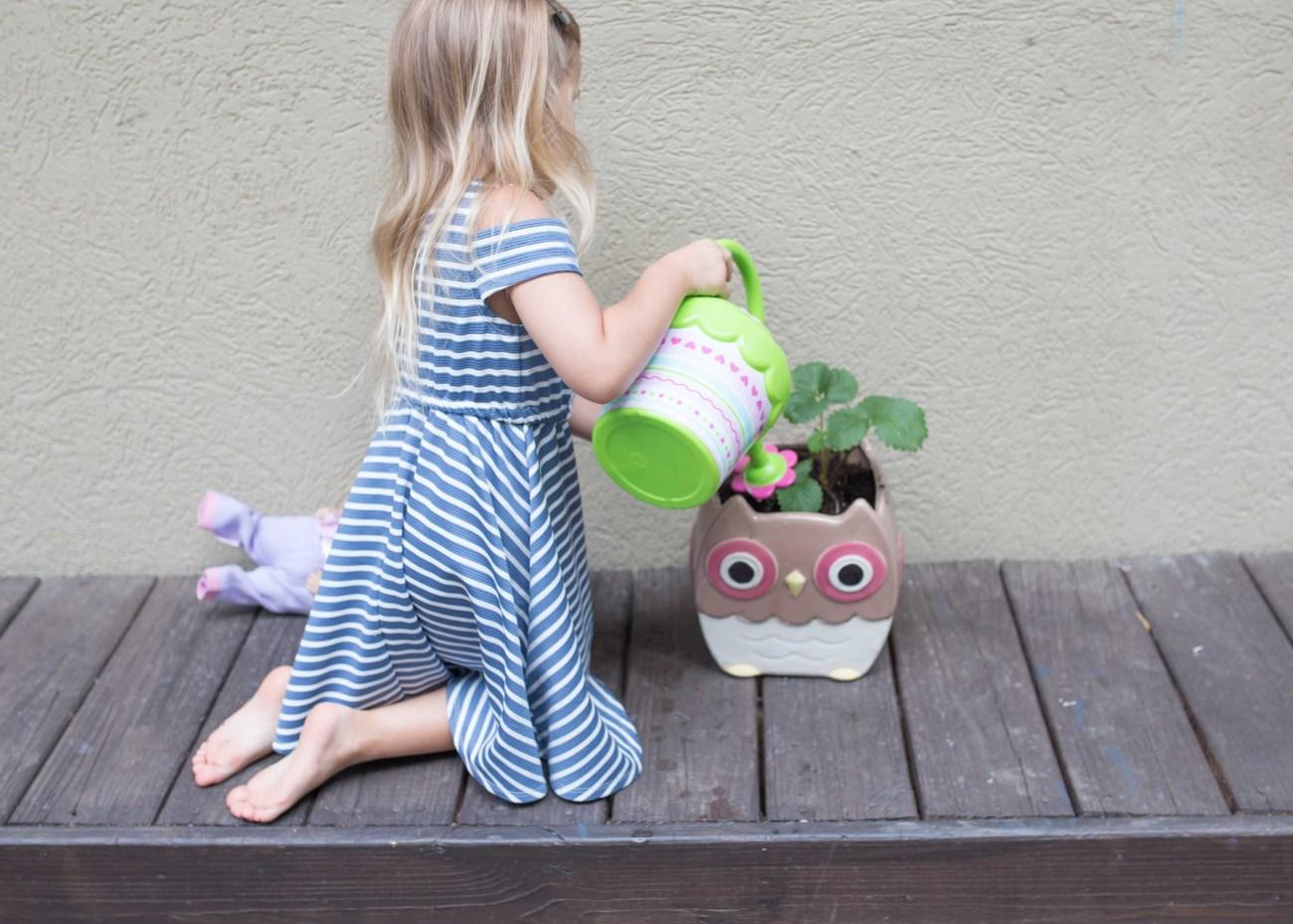 toddler girl watering plant gardening