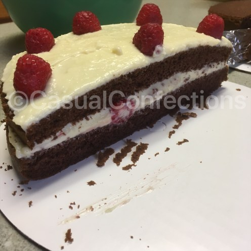 """Pastry cream and raspberries in a torted 9"""" round of devil's food cake."""