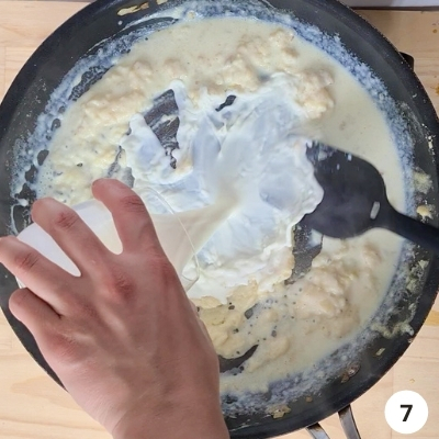 milk slowly being added into skillet of butter and flour mixture