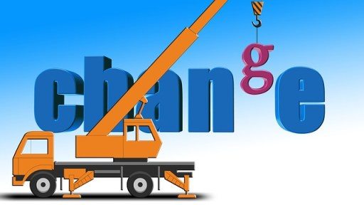 crane lifting the letter G into place in the word change