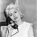 Debbie Harry using a rotary telephone.