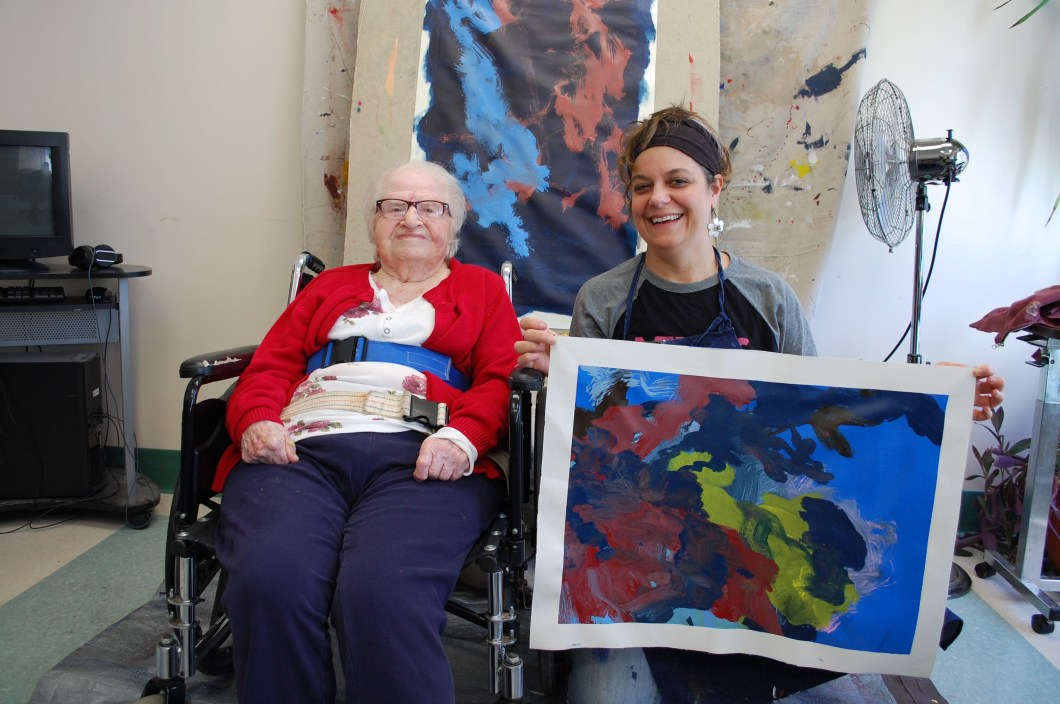 CATA artist Ruthie sits in a wheelchair next to Faculty Artist Stefanie, who holds Ruthie's new painting and smiles. The painting is abstract with broad strokes of red, dark blue, and yellow paint on top of a light blue background.
