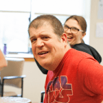 White man turned towards the camera in a red shirt, smiling.
