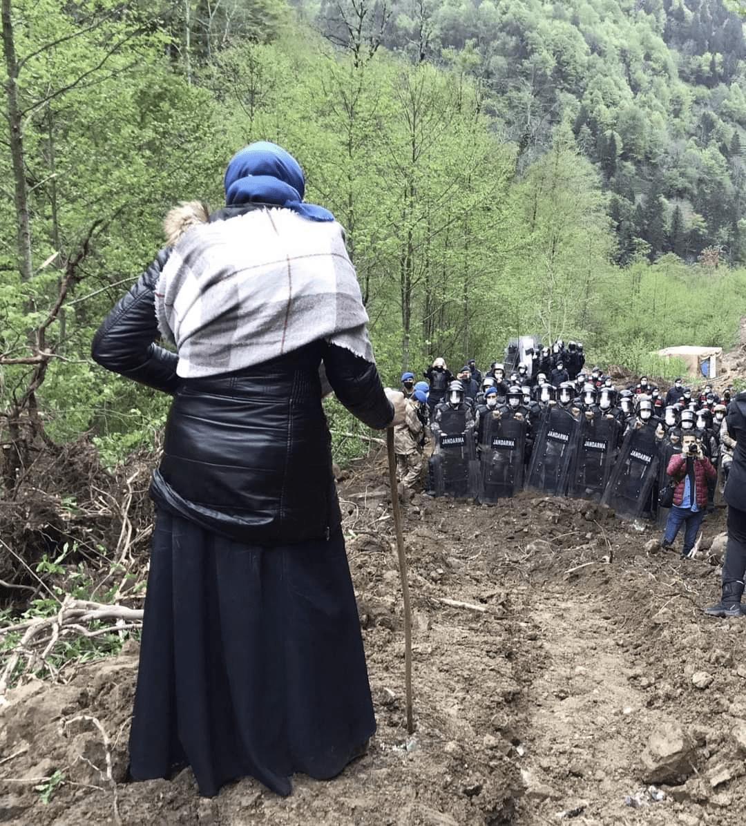 Turkse vrouwe met wandelstok staat voor een politie barricade