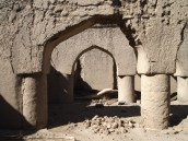 the arches and columns inside the large mosque at the far end of the village