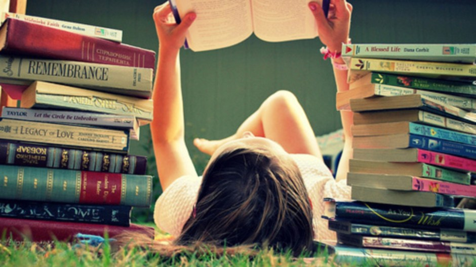 A girl reading a book with a bunch of books beside her. Image Source: Obvious. Bookworms live longer.