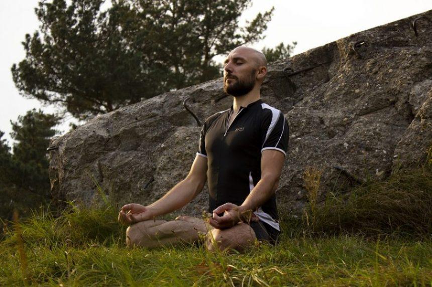 A guy meditating on grass