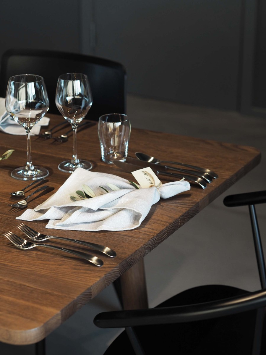 Danish dinner party in a dark, moody setting with green foliage and Georg Jensen silverware