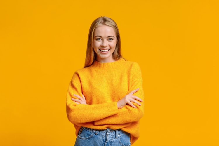 Portrait of beautiful young girl posing to camera with folded arms over orange background with free space