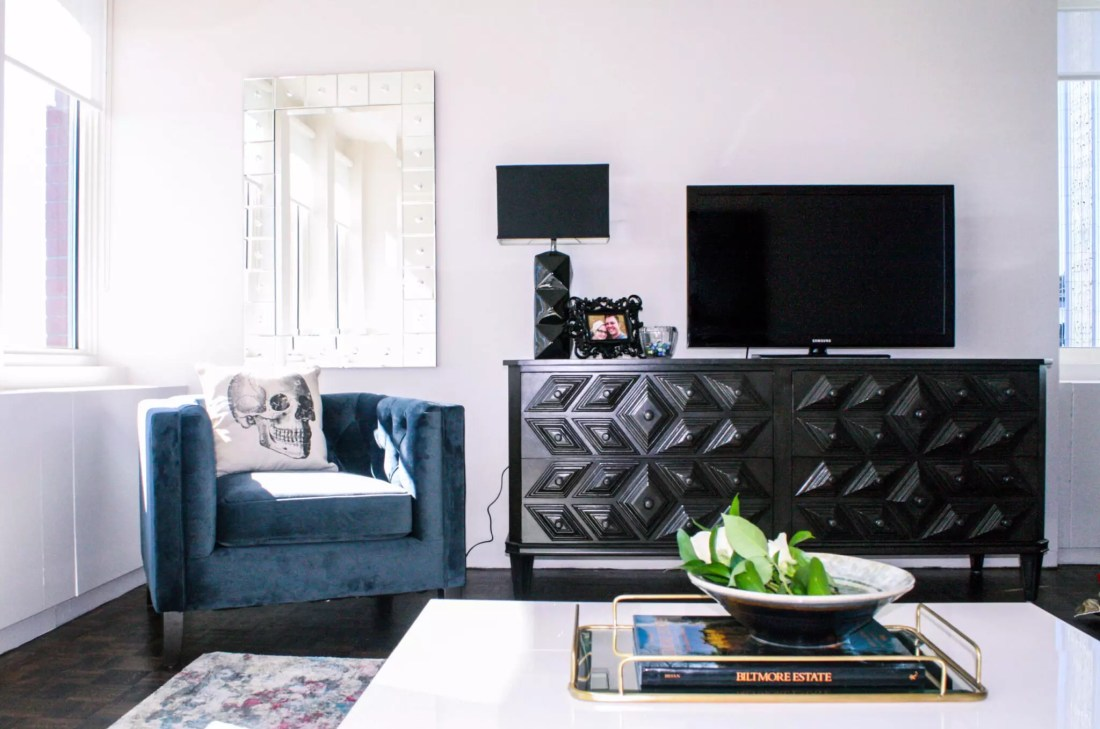 Blue velvet chair, skull pillow, geometric console, and storage coffee table