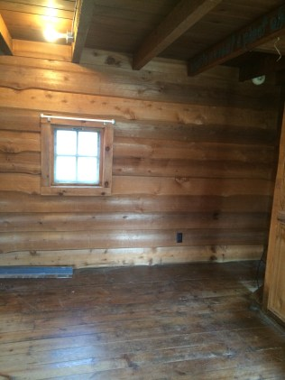 Small windows, smooth walls, exposed rafters in the main room.