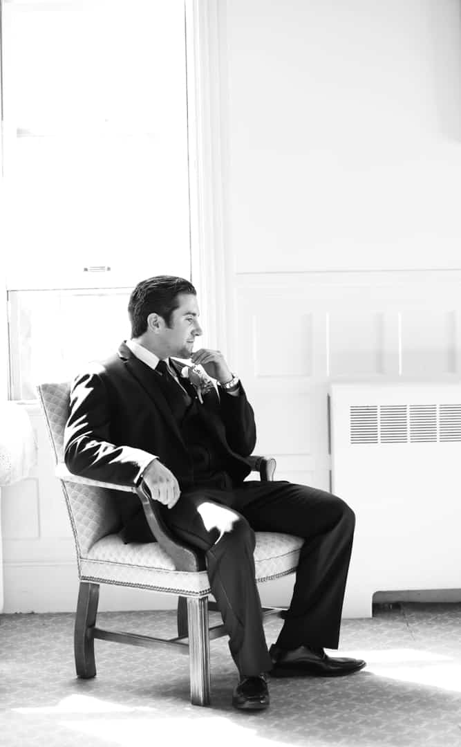 Groom sitting in chair, black and white