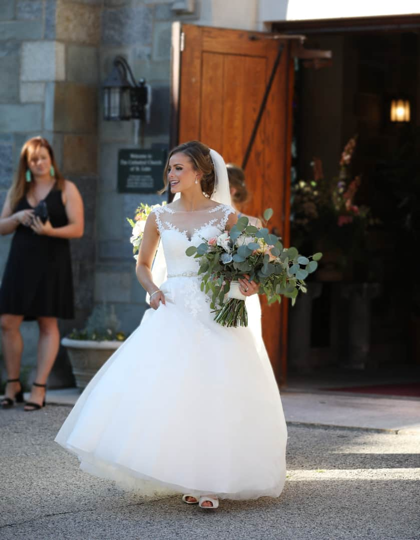 bride coming out as a wife, hand on hip, holding flowers outside of the church