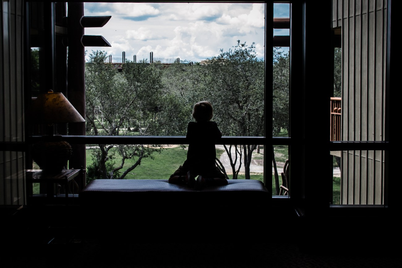 little boy looking out window disney animal kingdom lodge {virginia beach lifestyle newborn child couples family engagement photographer}