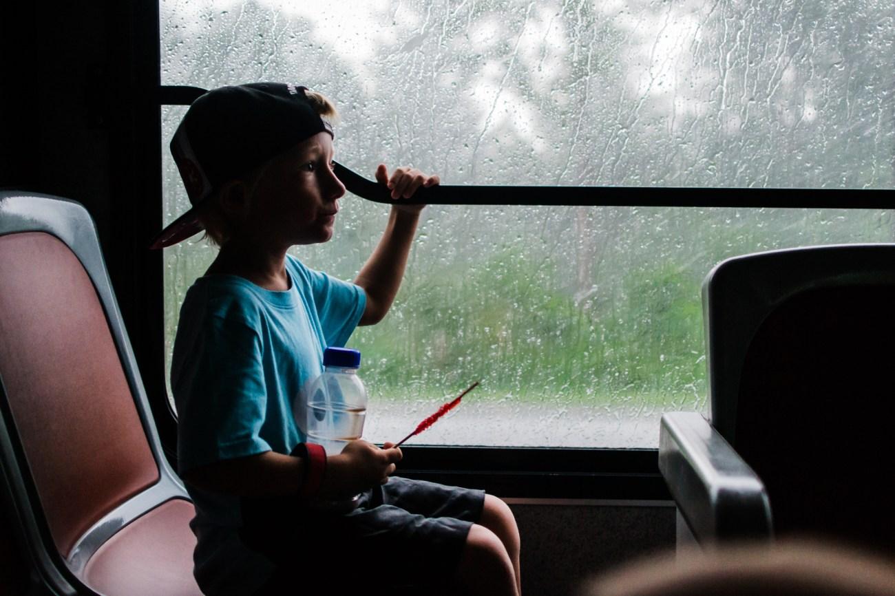 little boy sitting on disney bus rainy window {san diego lifestyle newborn baby child family photographer}