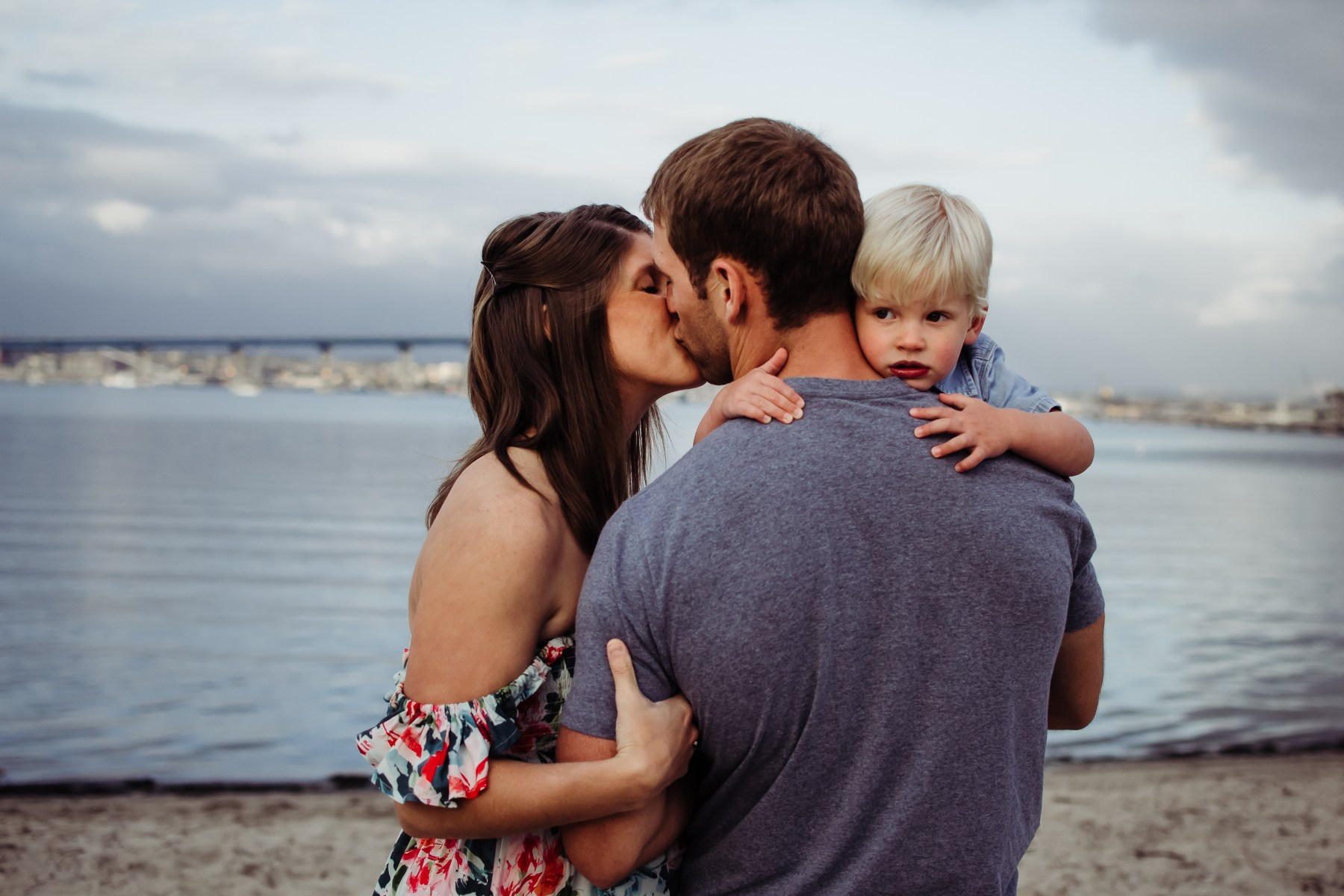 boy looking over dads shoulder while mom kisses him cordonado california {san diego newborn baby child family couples photographer}