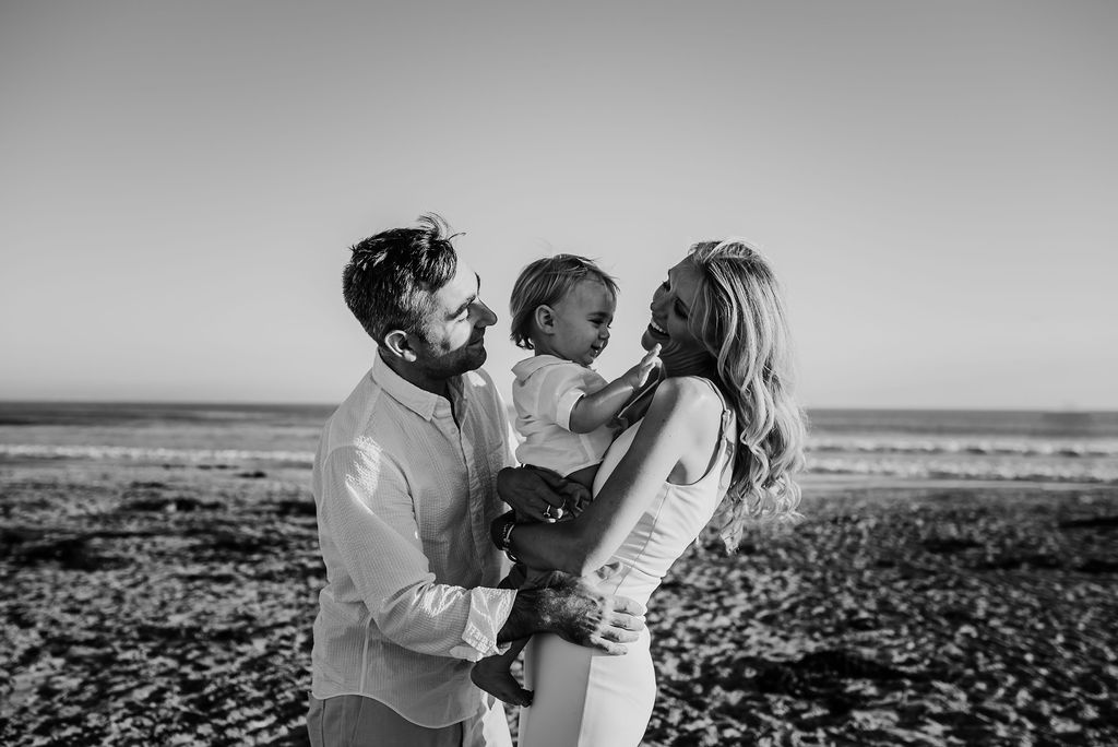 mom and dad smiling at baby boy sitting in sand breakers beach coronado{virginia beach chesapeake lifestyle child couples family military homecoming photographer holistic healer transformational mentor}