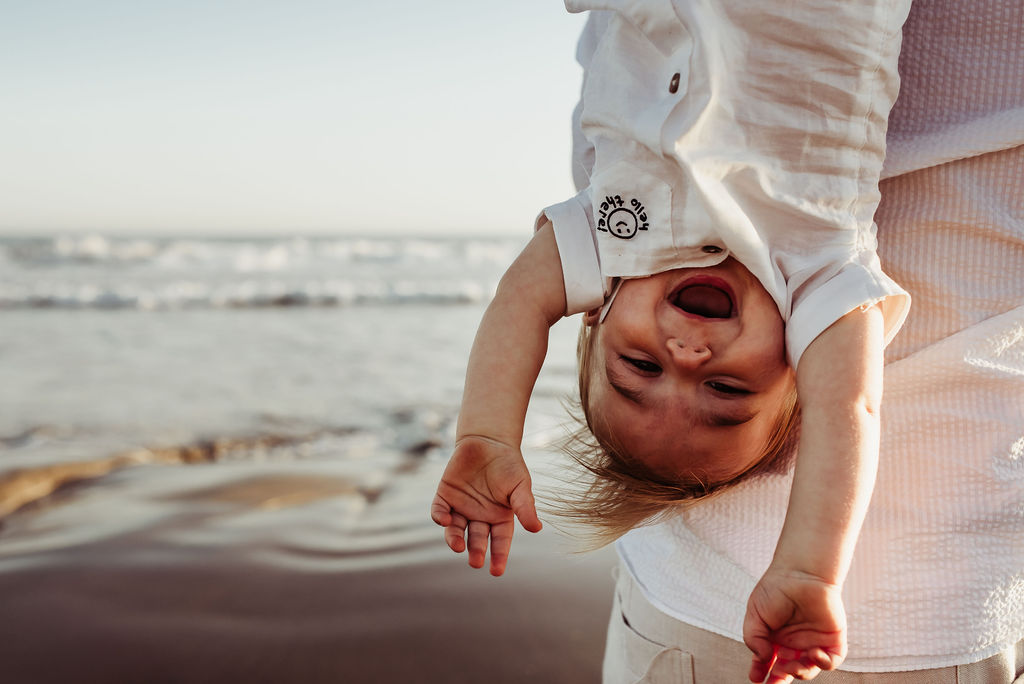 mom and dad smiling at baby boy laughing hanging upside down breakers beach coronado{virginia beach chesapeake lifestyle child couples family military homecoming photographer holistic healer transformational mentor}