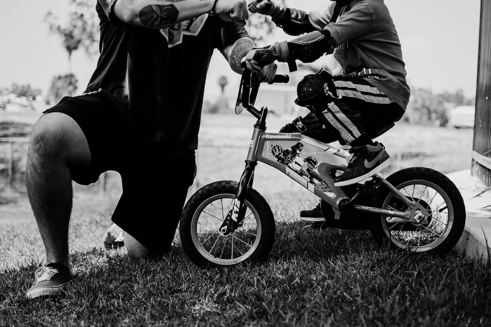 father giving son knuckles riding two wheeler bicycle {virginia beach lifestyle newborn child couples family maternity engagement photographer}