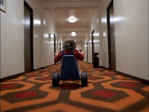 Child riding big wheel in hallway in the shining