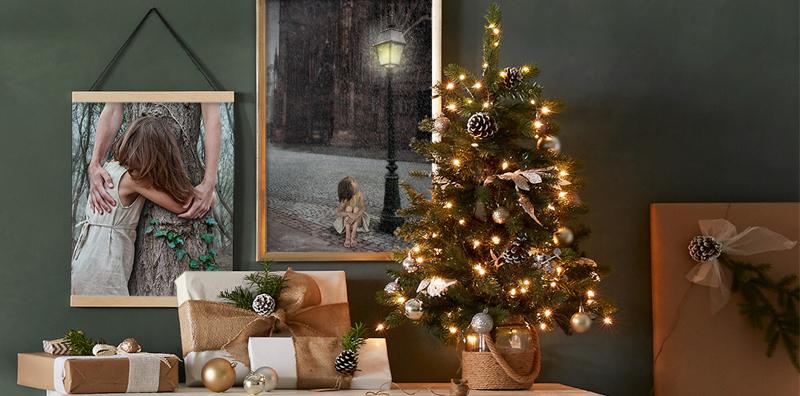 Étagère avec sapin de cadeaux de Noël, au mur deux photographies.