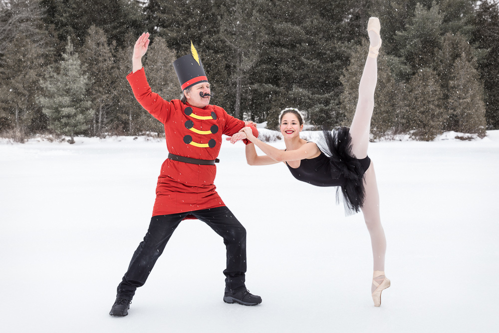 Photographie homme déguisé en Casse-noisette à côté d'une jeune ballerine en tutu noir dans un décor de neige.