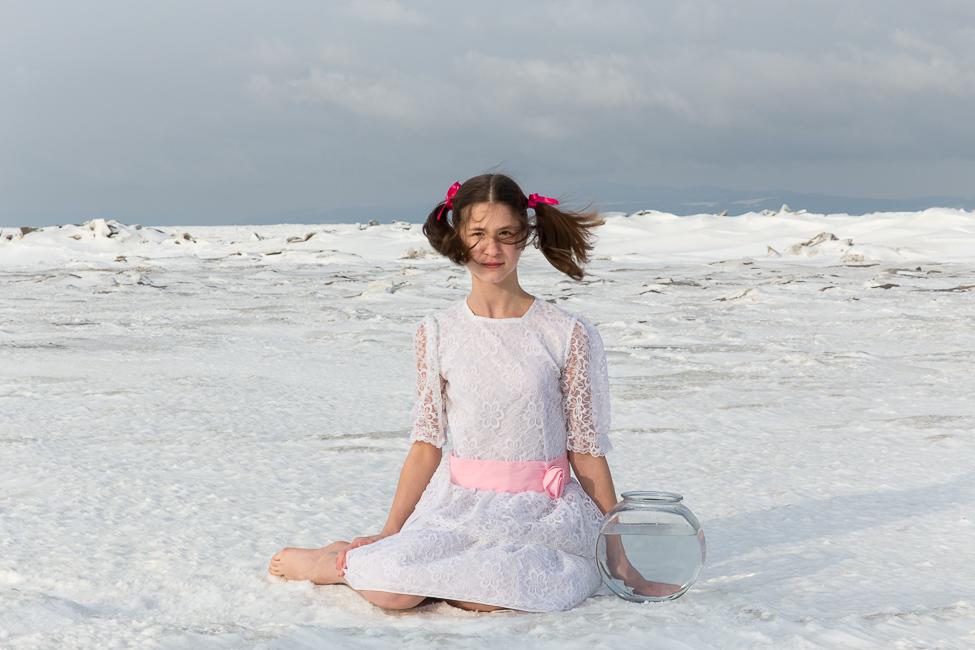 Une adolescente en robe d'été blanche est assise sur une banquise de neige au côté d'un bocal de poisson remplie d'eau, le vent balaie ses cheveux.