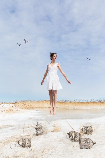 Jeune adolescente semble s'élever dans les airs au dessus de la neige parsemée de cage d'oiseaux