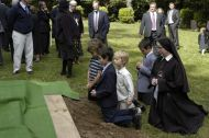 Boys are not afraid of dirt! Here, they show this in a pious way, as Sister Mary Joseph kneels in the grass.