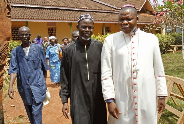Archbishop Dieudonne Nzapalainga of Bangui, Central African Republic, right, walks with Imam Oumar Kobine Layama, center, in Bangui, after a meeting of religious representatives, Bangui residents and African and French peacekeeping forces Feb. 10.  (CNS photo/Luc Gnago, Reuters)
