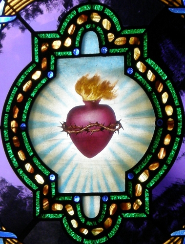 detail of a stained glass rose window of the Sacred Heart, date and artist unknown; Chapel of the Sacred Heart, Grand Teton National Park, Wyoming; photographed by Nheyob; swiped from Wikimedia Commons