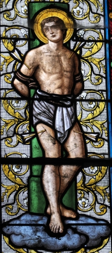 detail of a stained glass window of Saint Sebastian; signed Carmel du Mans et Hucher Rathois, date unknown; parish church of Notre-Dame in Bû, Center-Val de Loire, France; photographed on 15 August 2015 by GFreihalter; swiped from Wikimedia Commons