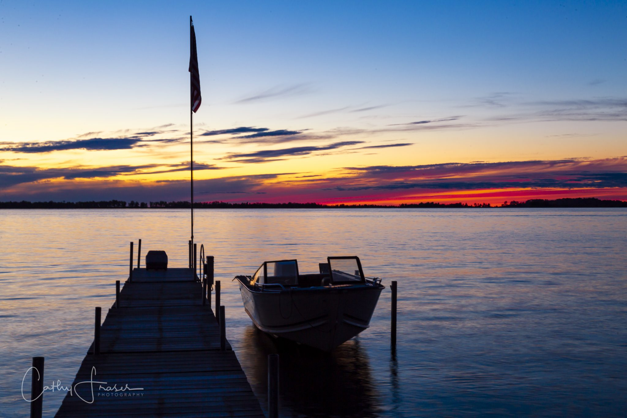 Landscape Photography of a boat docked at a lake in New York in front of a beautiful and colorful sunset