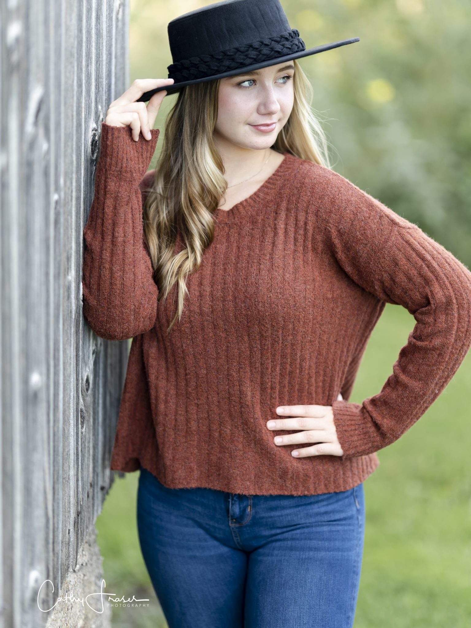 in natural light, girl wearing rust color sweater and a black hat leaning on an old barn