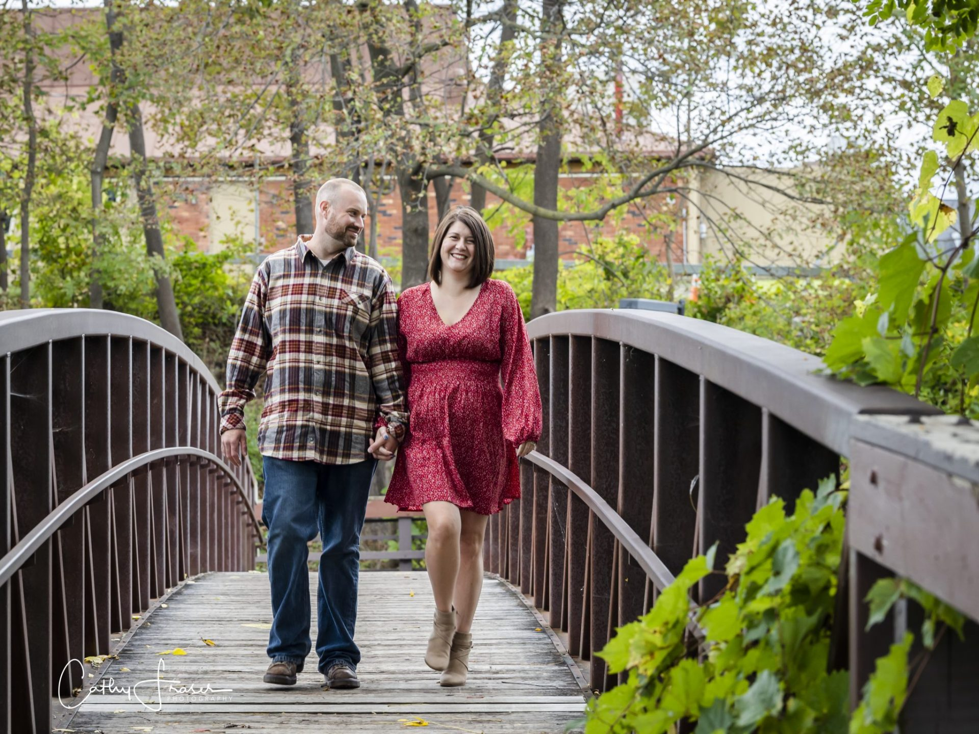 couple walking, Penn Yan, New York, natural light, husband and wife on footbridge, man in plaid flannel, jeans, woman in red dress