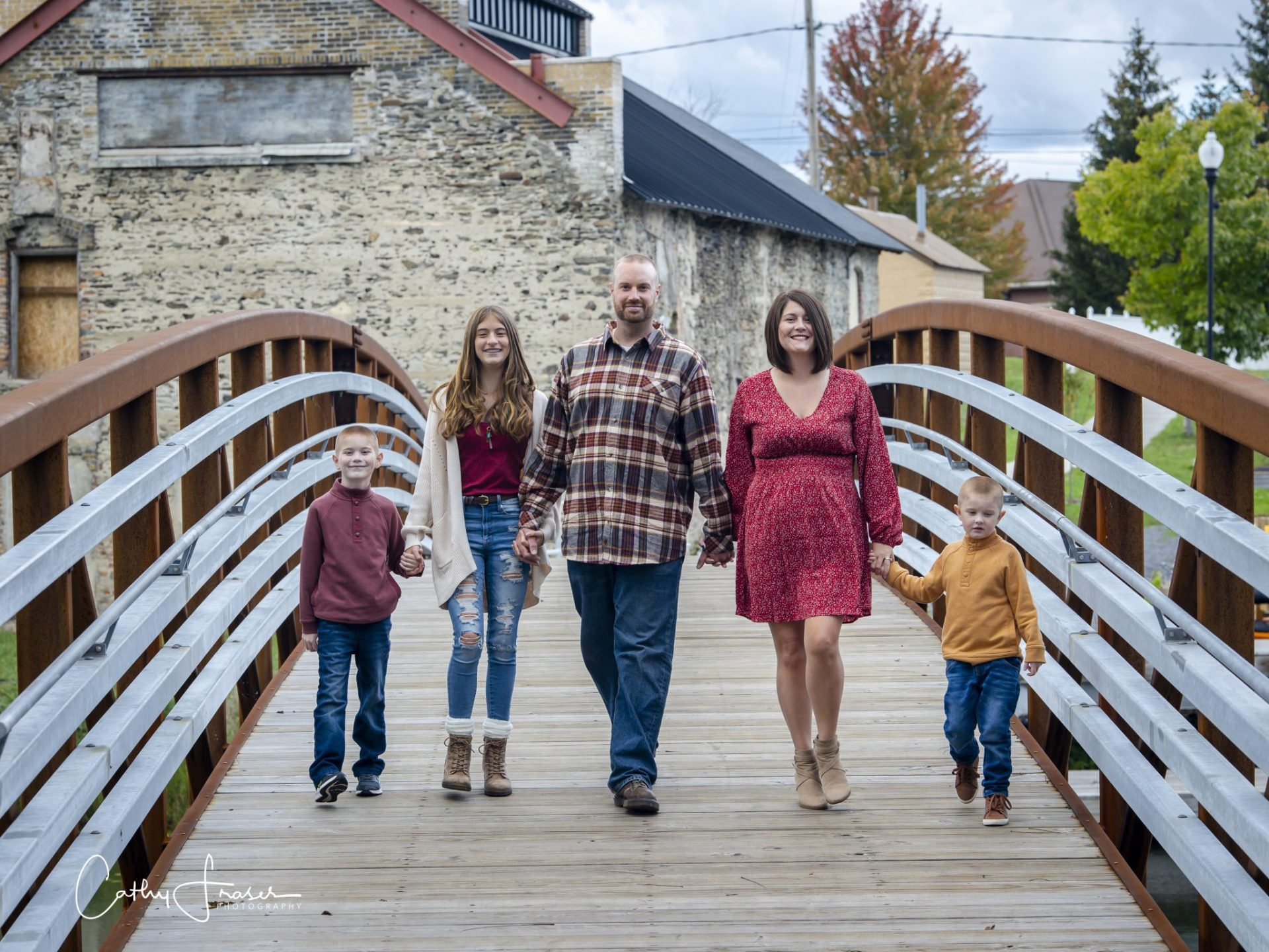 Family walking, holding hands, Penn Yan, New York, natural light, young boys, on footbridge wearing red sweater, and boy in gold sweater, teenage girl in red top, white cardigan, jeans and boots, man in plaid flannel, jeans, woman in red dress