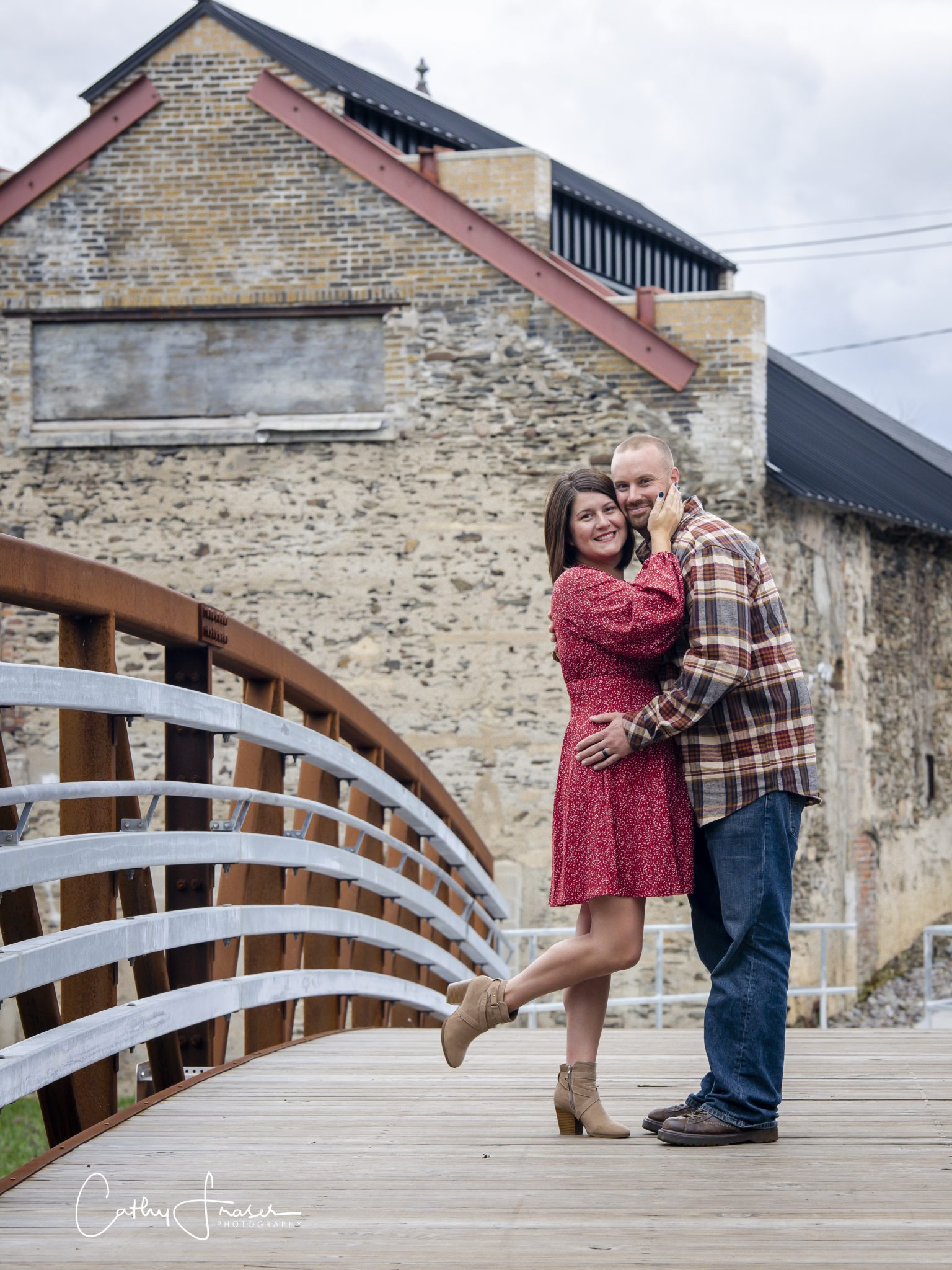 couple hugging, Penn Yan, New York, natural light, husband and wife on footbridge, man in plaid flannel, jeans, woman in red dress