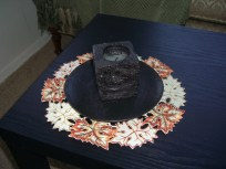 A cut-out doily provides a grand contrast on my dark table and sets the space for my Turf Candle.