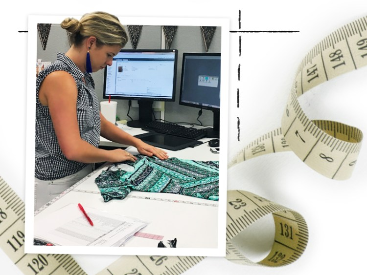 A young woman working at her desk measuring a shirt with a measuring tape